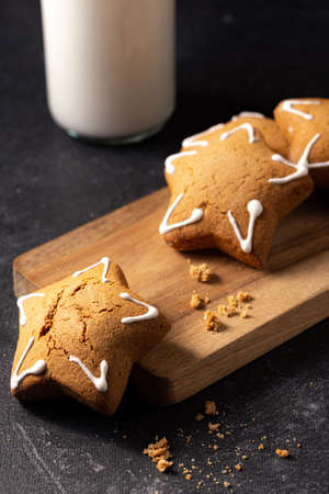 Handmade custard gingerbread in the shape of a star on a black background. Homemade baking. A bottle of milk in the background. Wooden plank. Baking crumbs.