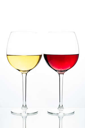 Two glasses with wine on a white background. Red wine. White wine. Apple juice. Cherry juice. Standard-Bild
