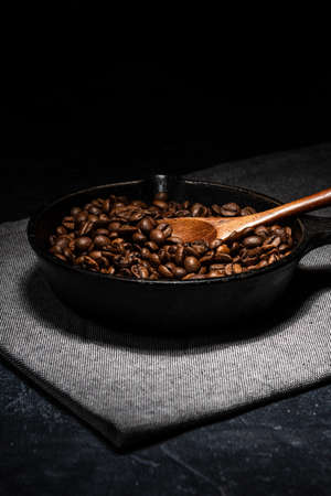 Freshly roasted coffee beans in a cast iron skillet. Linen napkin. A natural stone. Dark background.