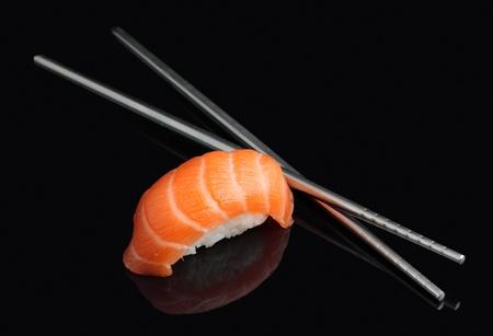 Sushi with chopsticks on black background