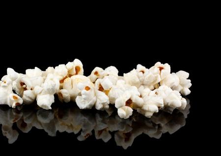 mucchio di popcorn su fondo nero con la riflessione