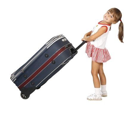 Child girl pulls big luggage
