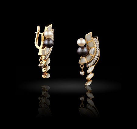 Pair of gold earrings on black background  photo