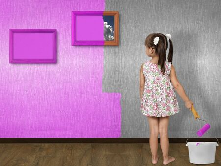 child girl doing repair, painting wall photo