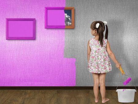 child girl doing repair, painting wall Stock Photo