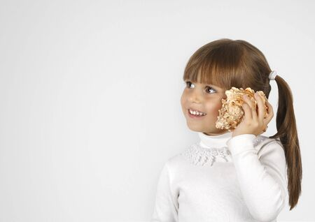 simulate: little girl with cockleshell simulate phone call Stock Photo