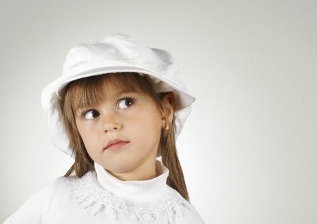 aside: child girl dressed a hat, closeup portrait
