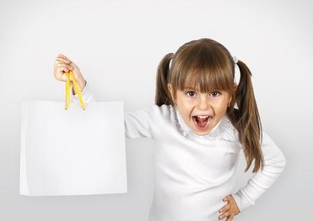 portret van geschreeuw kind meisje met het winkelen zak