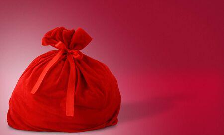 Santa gift bag on red background photo