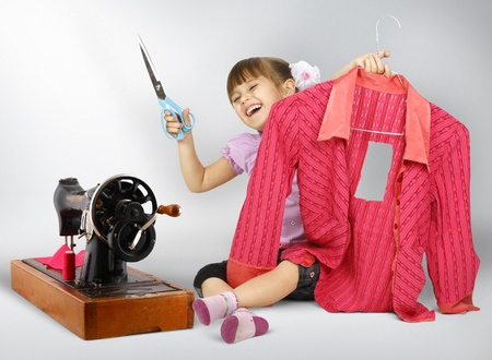 disobedient child: Little girl sewing , cuting dress Stock Photo