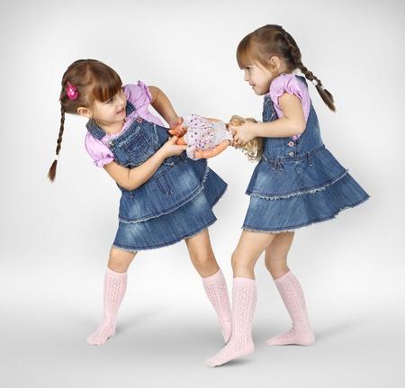 niñas gemelas: la lucha contra dos niñas pequeñas y la muñeca compartida Foto de archivo