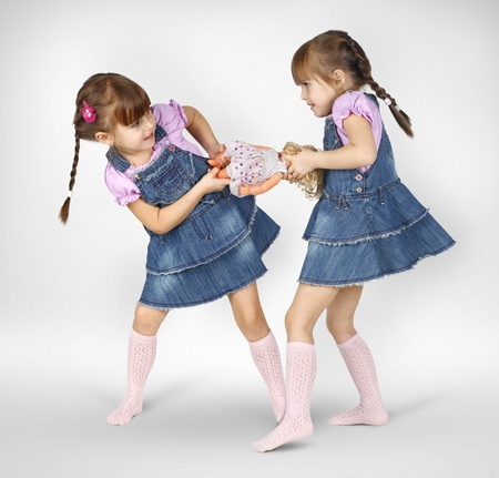 quarrel: little twin girls fighting and shared doll