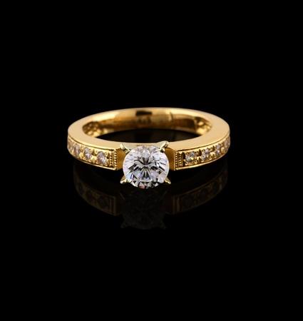 ring engagement: Anillo de oro con brillantes aislados sobre fondo negro Foto de archivo