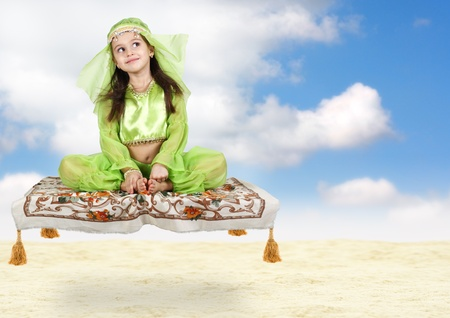 little arabian girl sitting on flying carpet with sky background