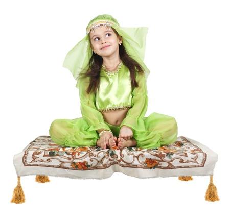 kleine Arabische meisje zittend op een vliegend tapijt op een witte achtergrond
