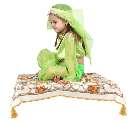 little arabian girl sitting on a flying carpet isolated on white background