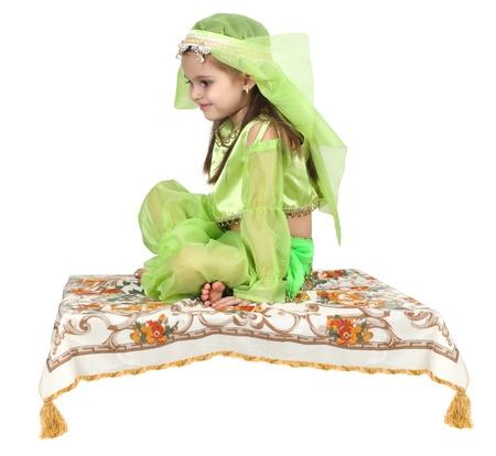 kleine Arabische meisje zittend op een vliegend tapijt geïsoleerd op witte achtergrond Stockfoto