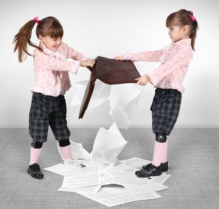 niñas gemelas: lucha contra niñas pequeñas y una maleta de doble compartida con los documentos Foto de archivo