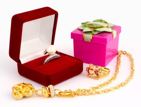 gioielli in oro e confezione regalo su sfondo bianco