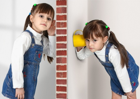 noise isolation: Little twin girls overhears, communications concept Stock Photo
