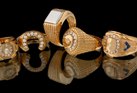 Gouden ringen met diamanten geïsoleerd op zwarte achtergrond Stockfoto