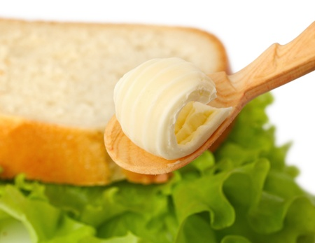 Butter curl on wooden spoon with bread on background Stock Photo - 12882551