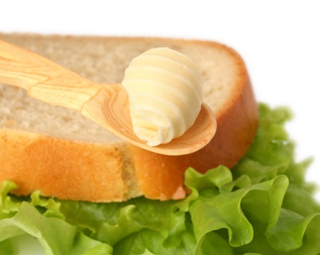Butter curl on wooden spoon with bread on background Stock Photo - 12882548