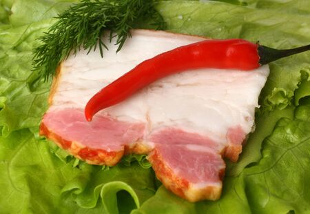 Raw fat bacon with pepper on lettuce Stock Photo - 12882555