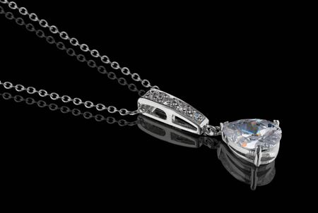 Diamond pendant with chain isolated on black background