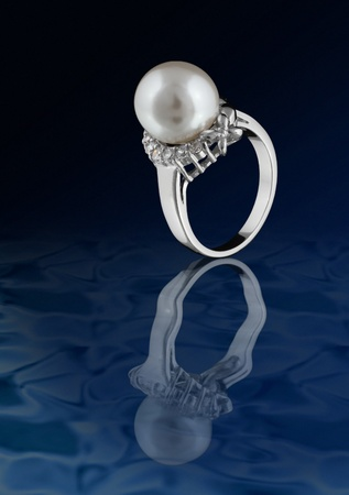 Ring with pearl on water reflection photo