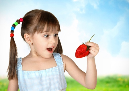 Funny surprised child girl with strawberry, field on background