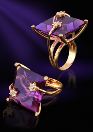 Gold ring with gem and diamonds on dark background Imagens