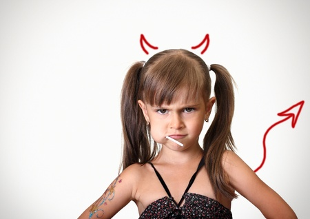 satan: Portrait of funny angry child girl with candy, behavior concept Stock Photo