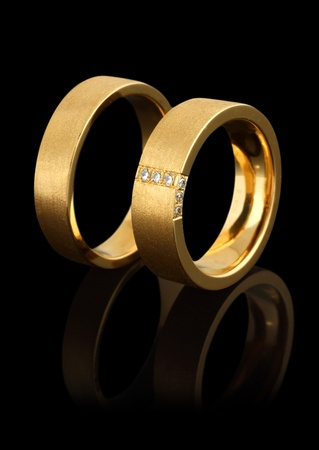 anelli di nozze d'oro con diamanti isolato su sfondo nero Archivio Fotografico