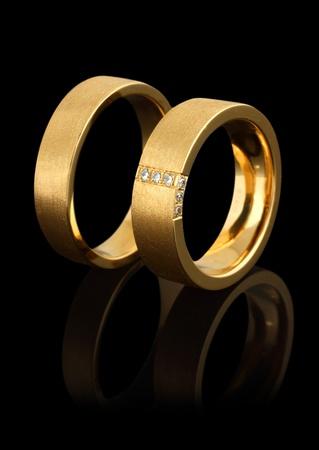 diamond jewellery: gold wedding rings with diamonds isolated on black background Stock Photo