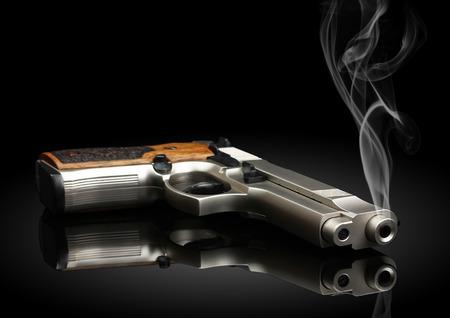 煙が黒の背景にクローム メッキの拳銃