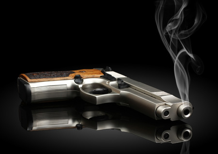 Chromed handgun on black background with smoke Stock Photo
