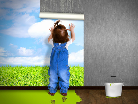 ecology concept: Funny child hanging wallpaper, doing repairs. Eco house concept.