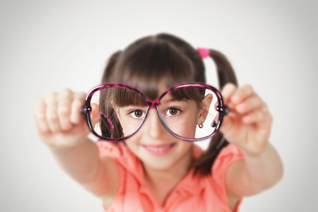 little girl holding eyeglasses, health eyesight concept. Soft focus Standard-Bild