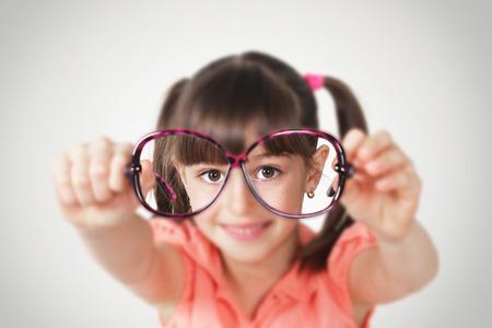 vision problems: little girl holding eyeglasses, health eyesight concept. Soft focus Stock Photo