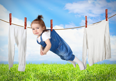 Funny child hanging on line with clothes, laundry creative concept