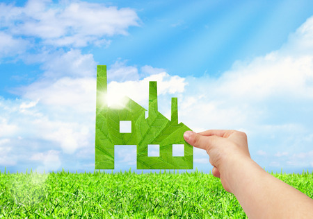 Hand hold factory iconon field and blue sky background, Eco green factory concept Foto de archivo