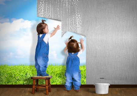 Little twins doing repair at home, hanging wallpaper. Renovation concept. Stock Photo
