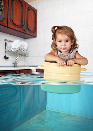 Funny little child swim in pan in the flooded kitchen, mess creative concept Stock Photo