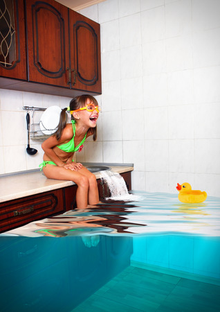 child swimsuit: Child girl make mess, flooded kitchen imitating swimming pool, funny concept Stock Photo
