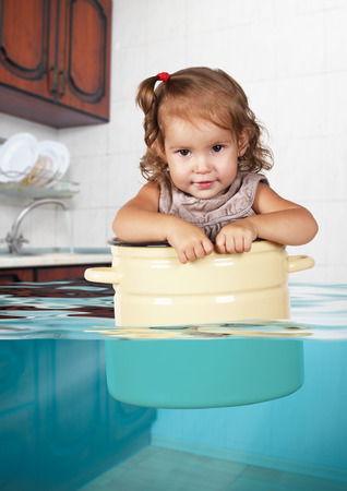 misbehavior: Funny little kid swim in pan in the flooded kitchen, rowdy creative concept Stock Photo