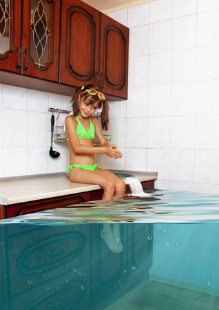 unattended: Child girl make mess, flooded kitchen imitating swimming pool, funny concept Stock Photo