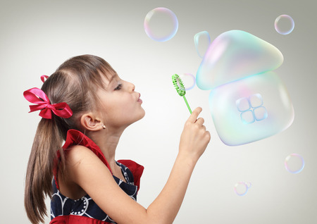 Child girl blowing soap bubble forming house, creative habitation concept Stock Photo