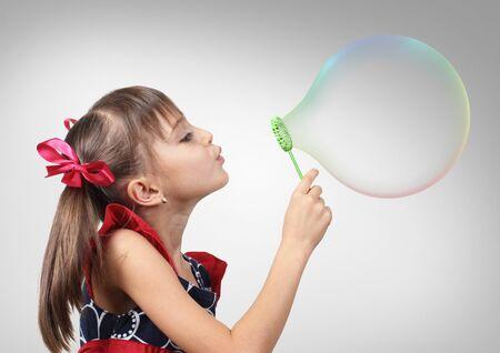 portrait studio: Portrait of child girl blowing big soap bubble, studio shot