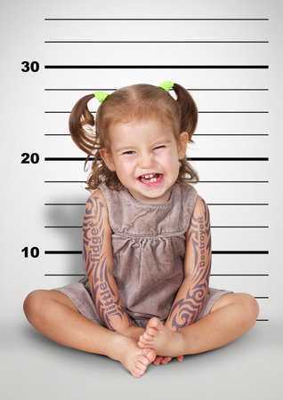 disobedient child: Mugshot, funny naughty baby with tattoo, disobedient child concept.
